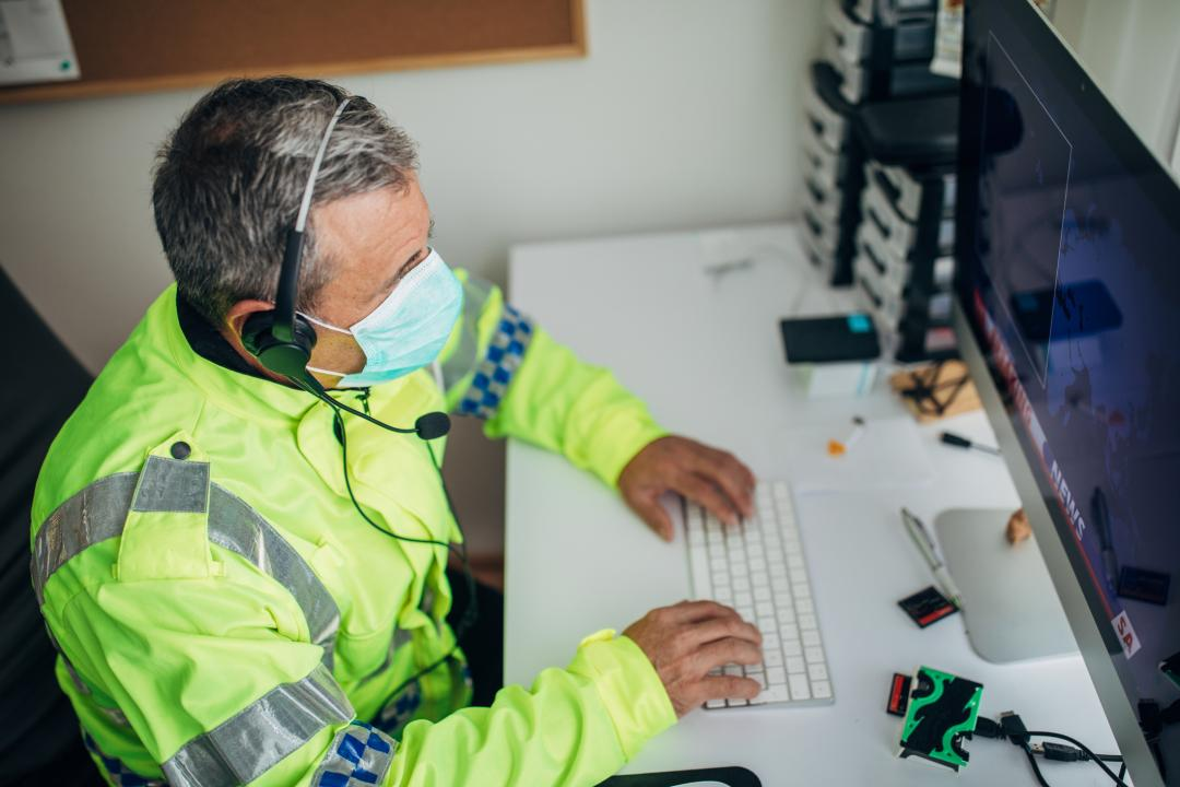 Older police officer operating a computer