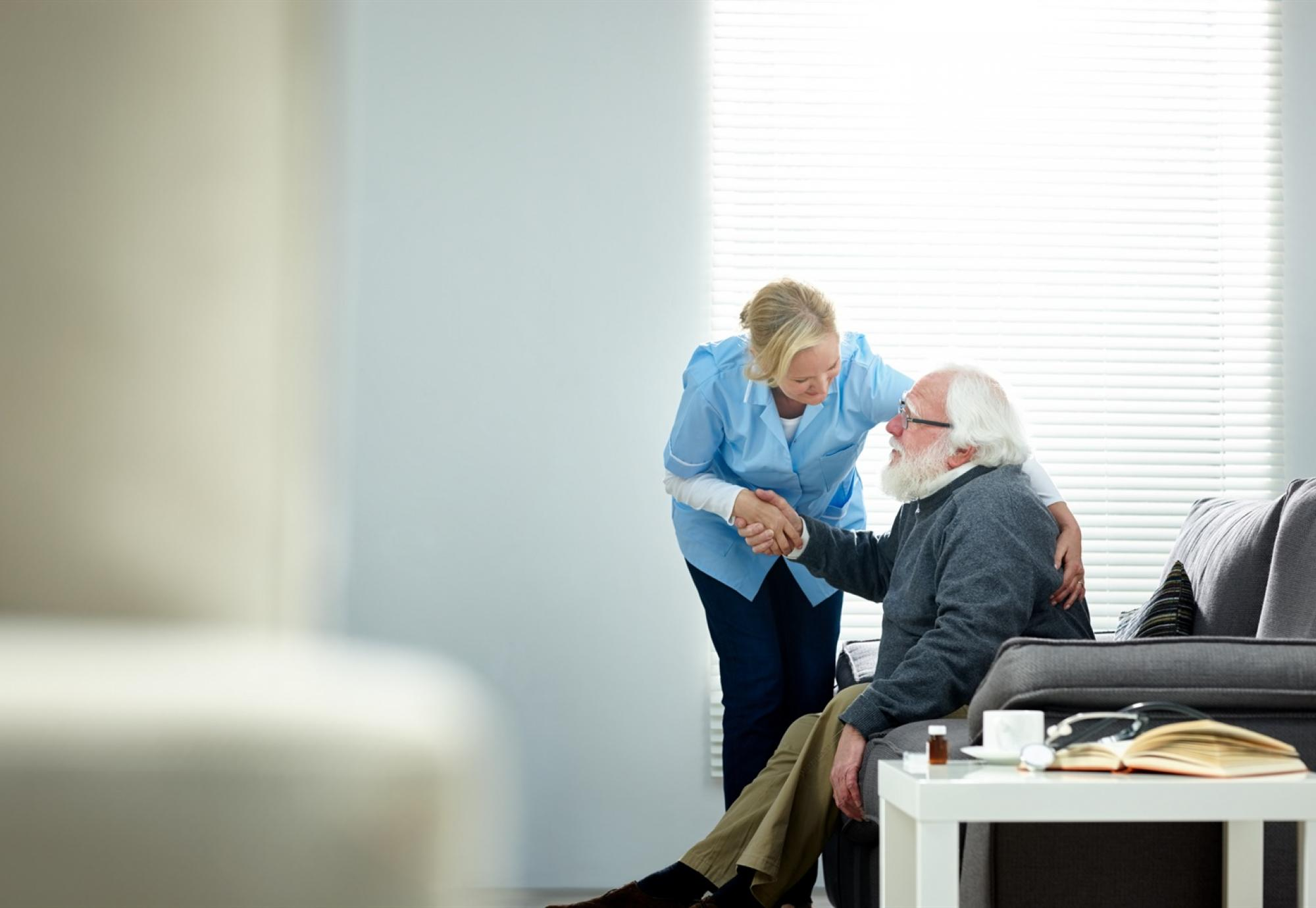 Carer helping elderly man