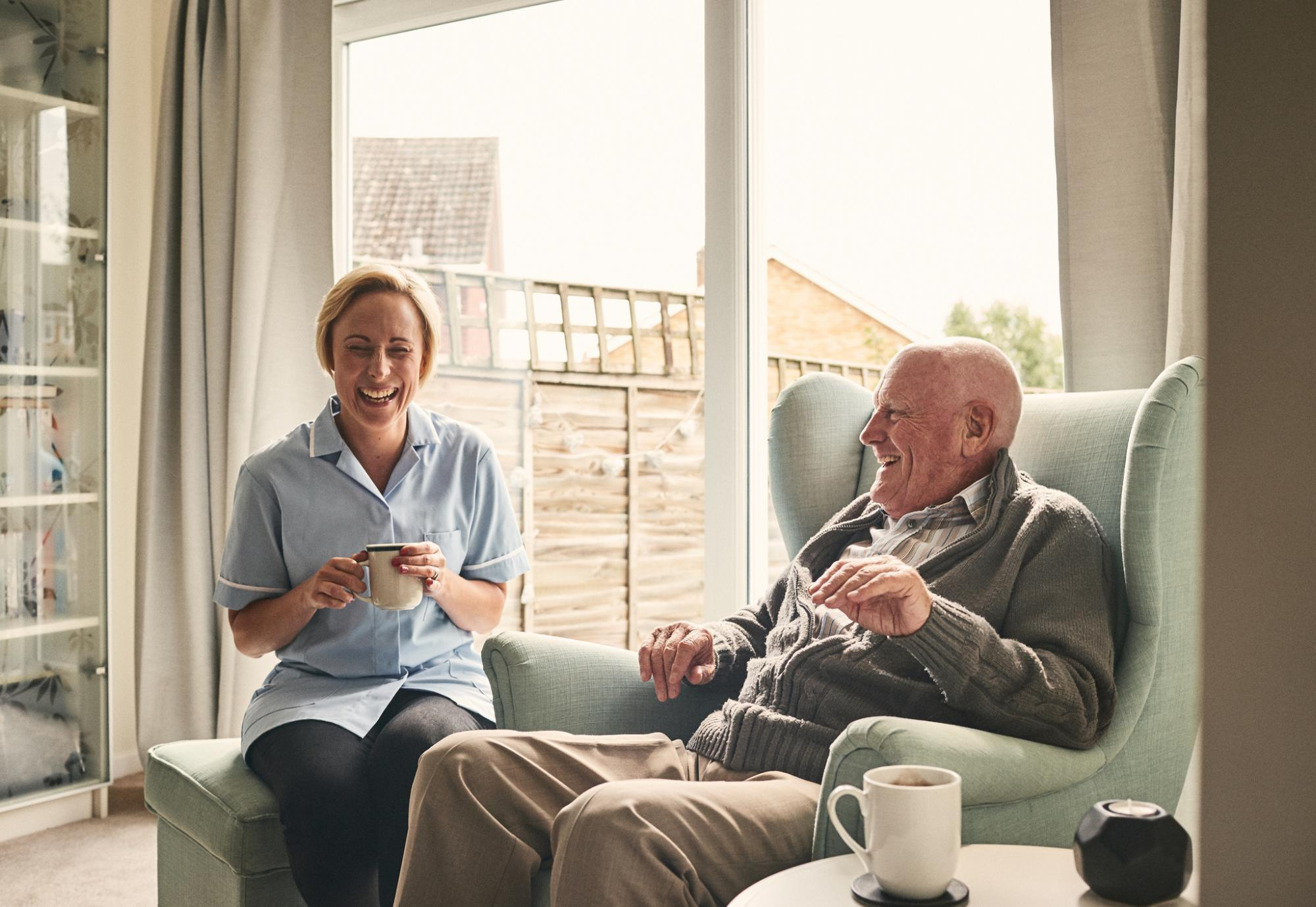 carer nurse laughing with older gentleman