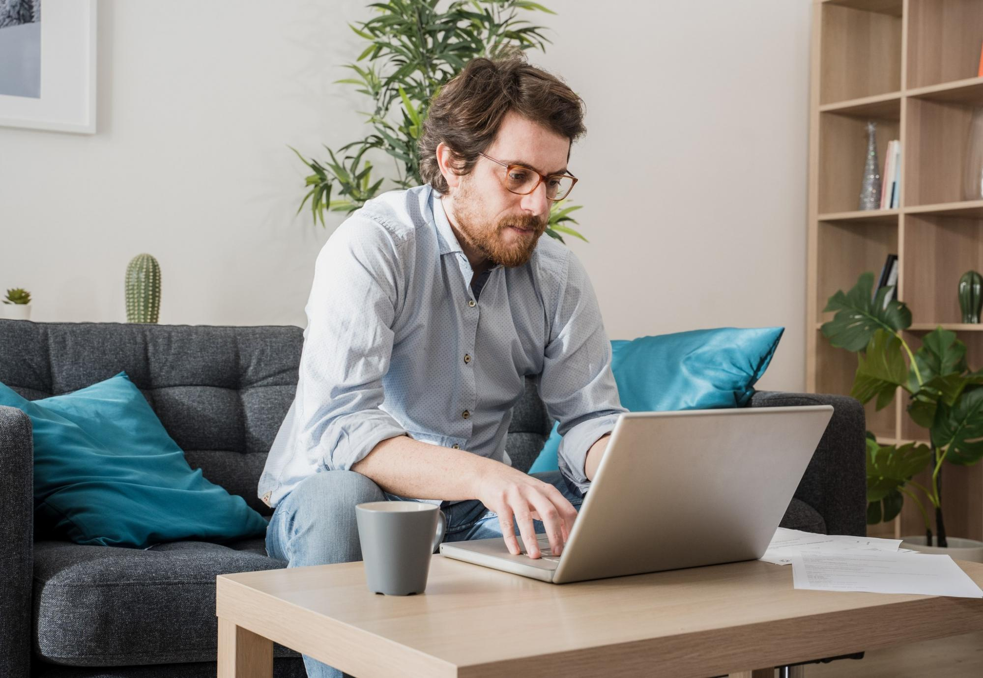Man sits at computer, working from home.