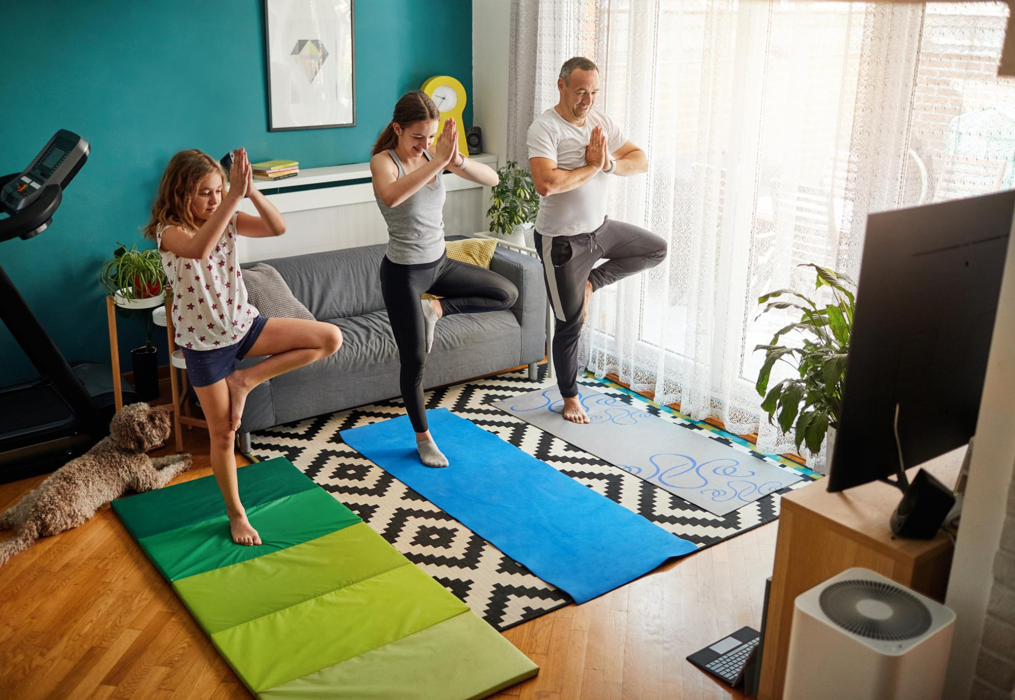 Father and his two daughters practicing yoga with online classes.
