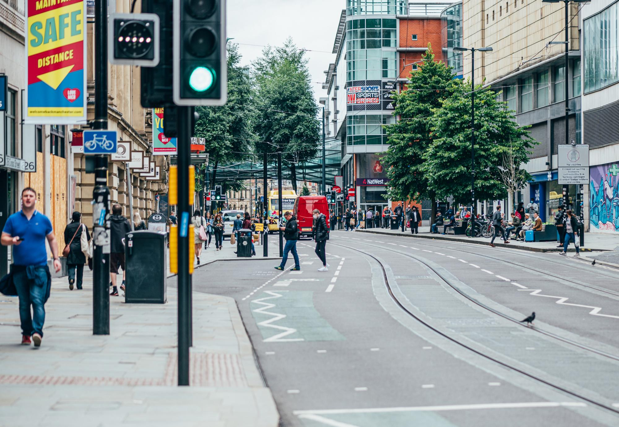 Busy Manchester street with pedestrians on the pavement.