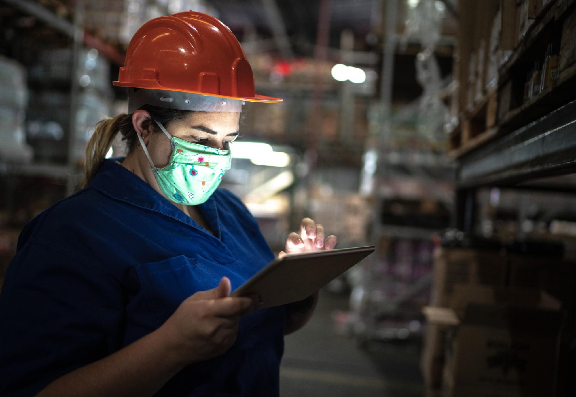 Girl in warehouse working on a tablet.