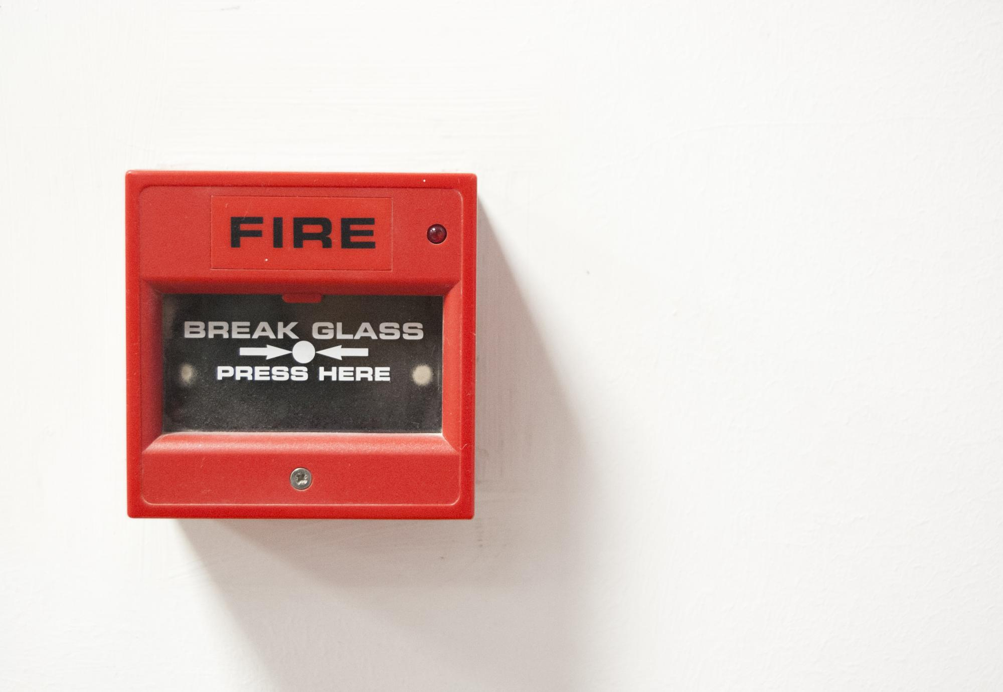 Fire alarm sits on wall ready to be activated.