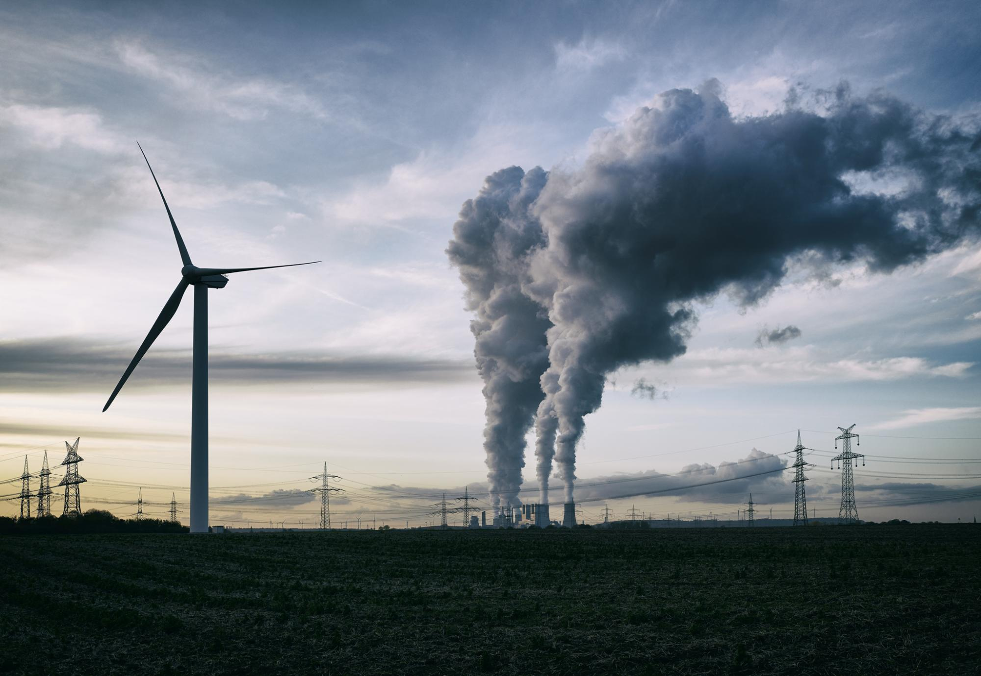 Wind turbine stands in the foreground as coal power station puts steam into atmosphere.