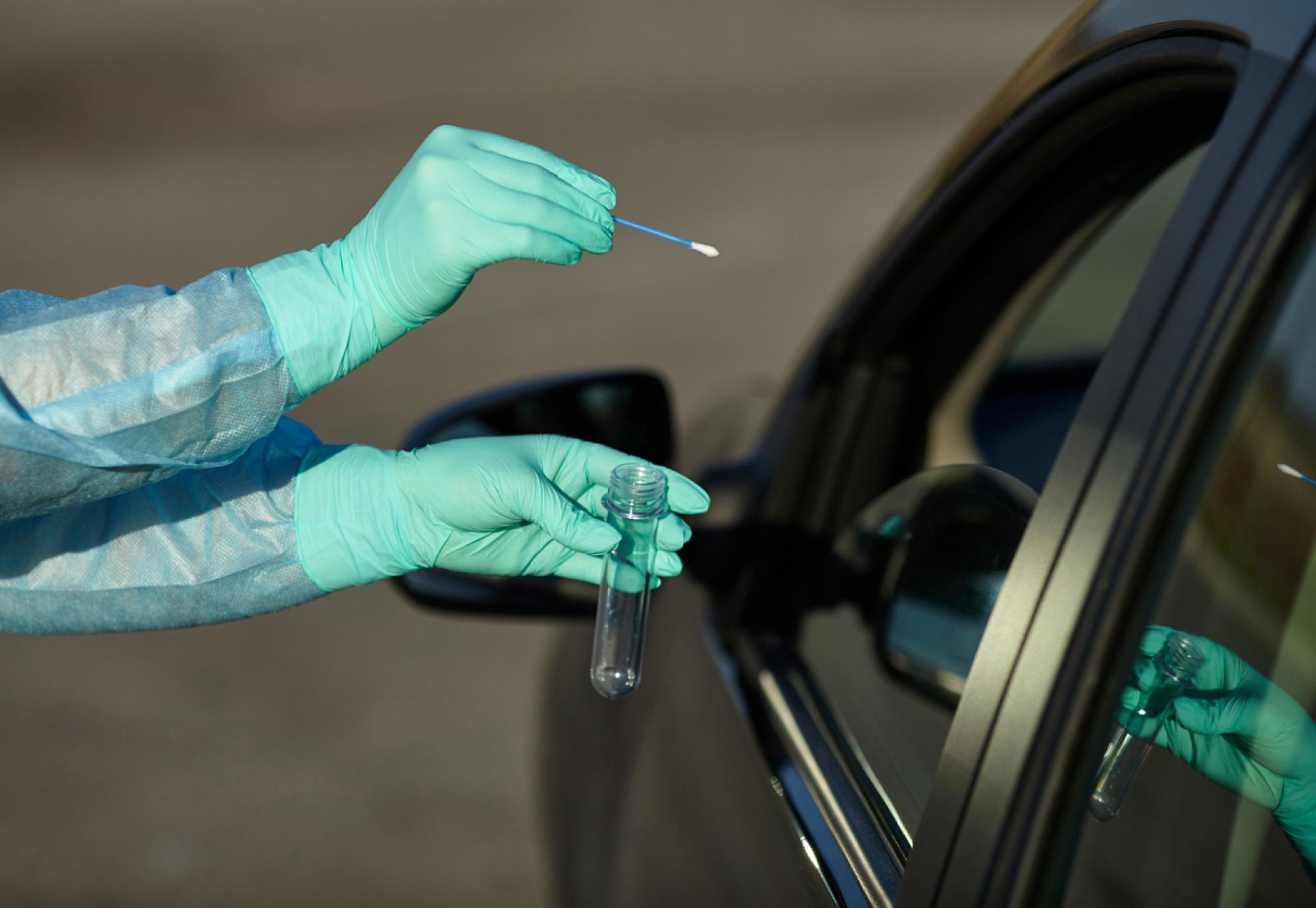 Gloved person swabs person in car for Covid.