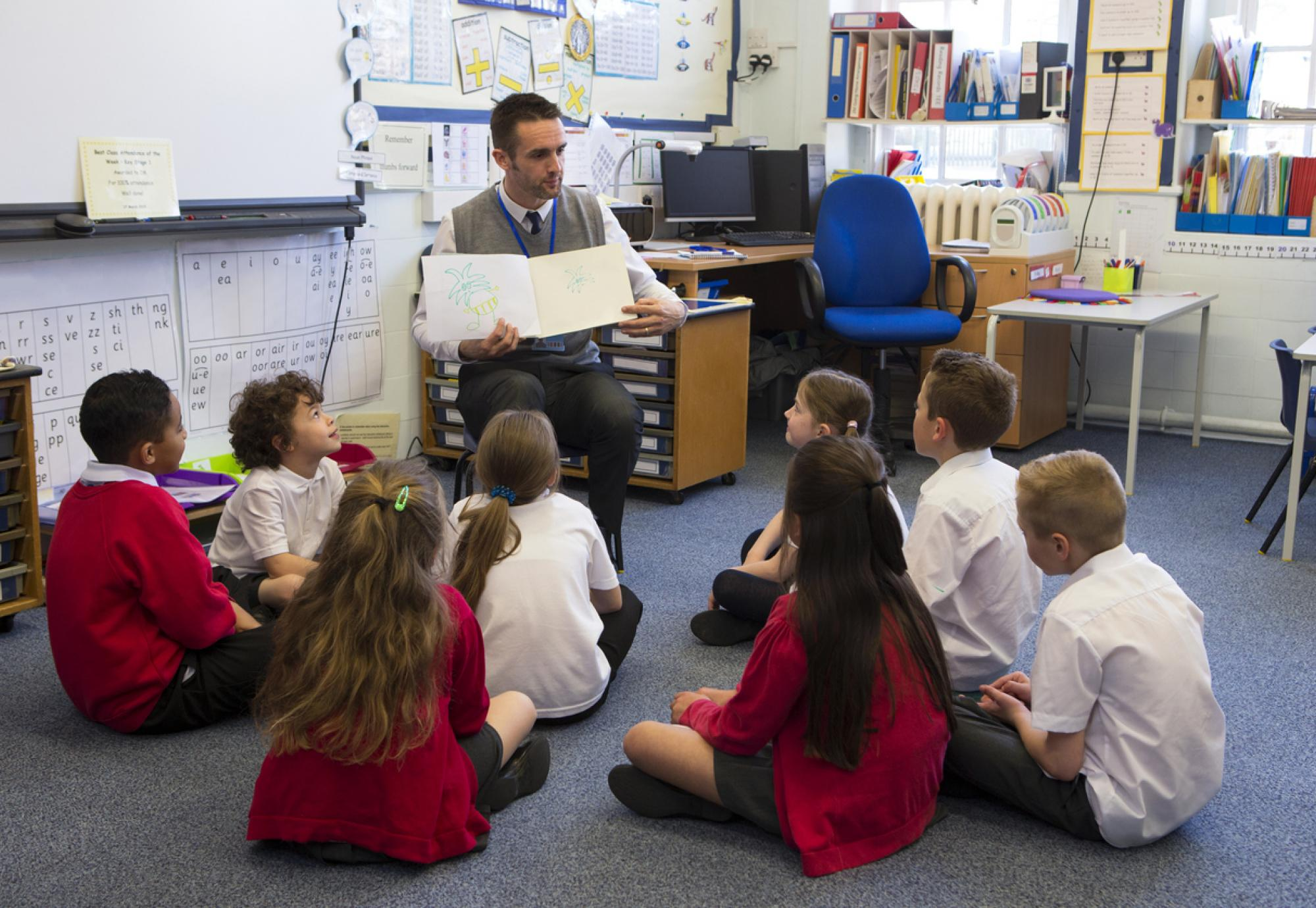 Children sit with teacher as he reads a story.