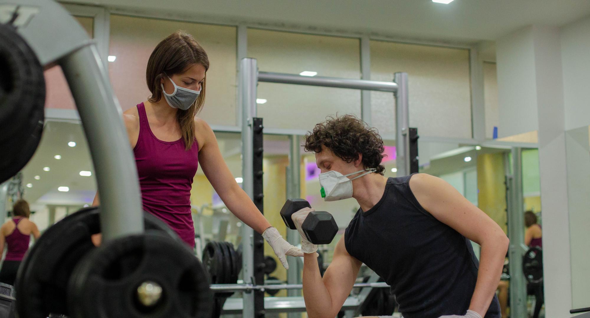 2 people training in a gym while socially distanced and wearing PPE.