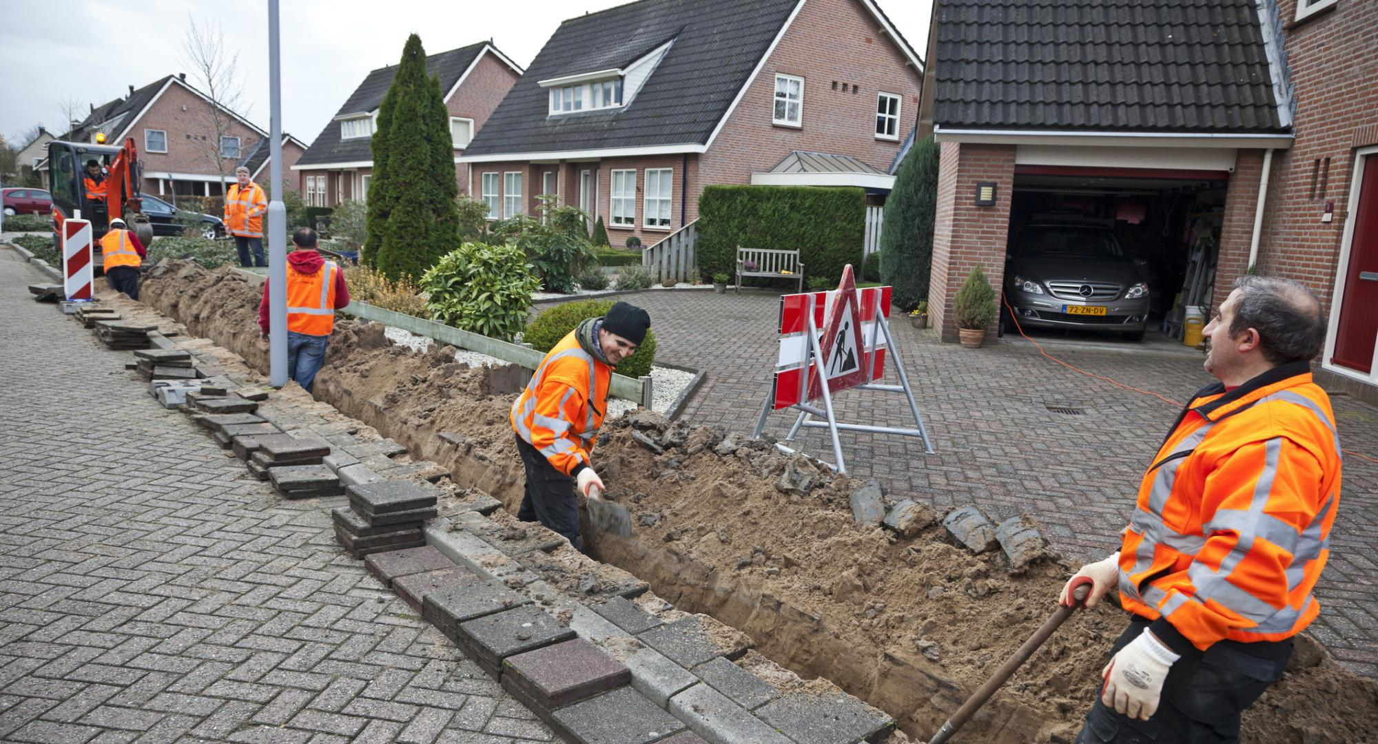 Workmen bring up pavement to lay fibre optic cables.