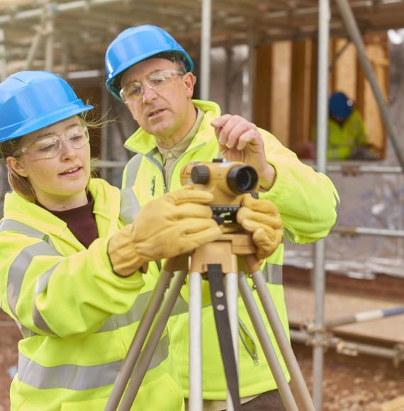 A female construction worker stands behind a builder's level on a building sit