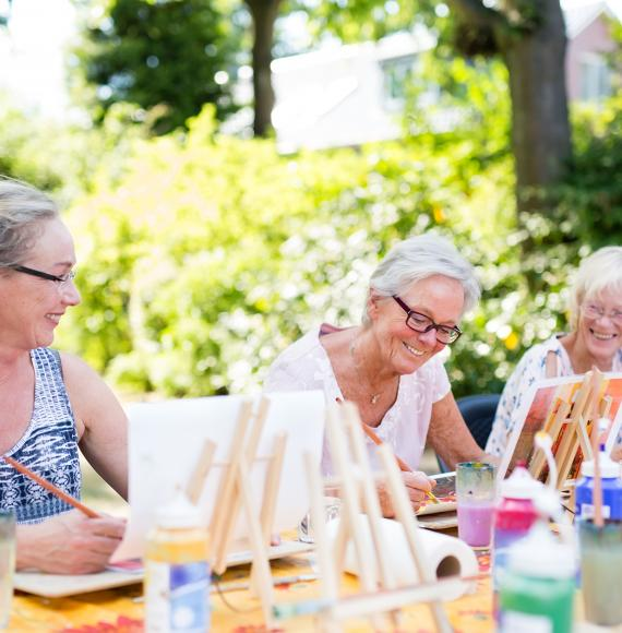Group of happy elderly women attending an outdoor art class in a garden.