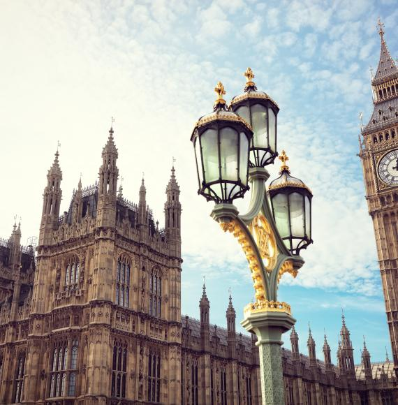 Big Ben in London with the houses of parliament and ornate street lamp.