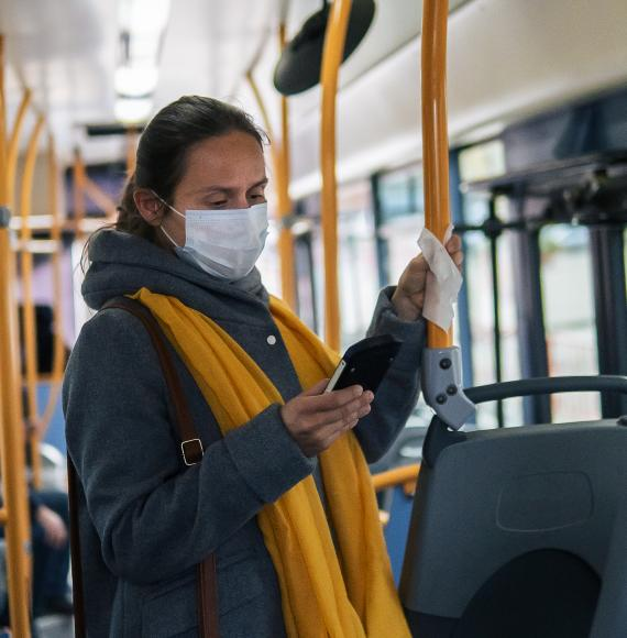 Woman stands  on bus in mask