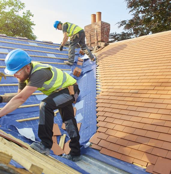 Builders tiling a roof