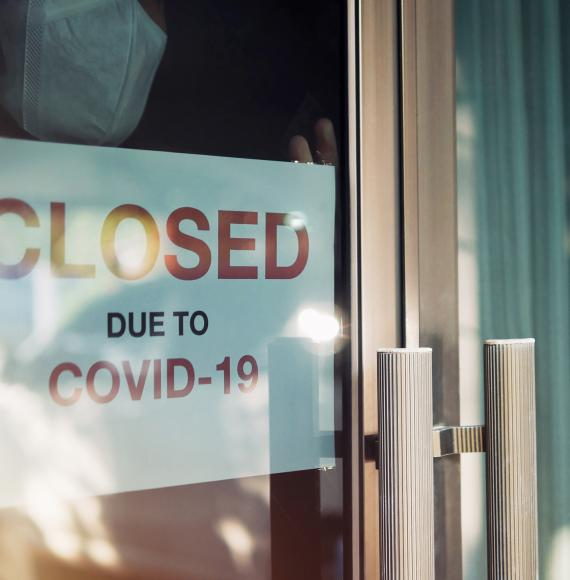 "Person puts sign up that says ""Closed due to Covid"" in their shop window."