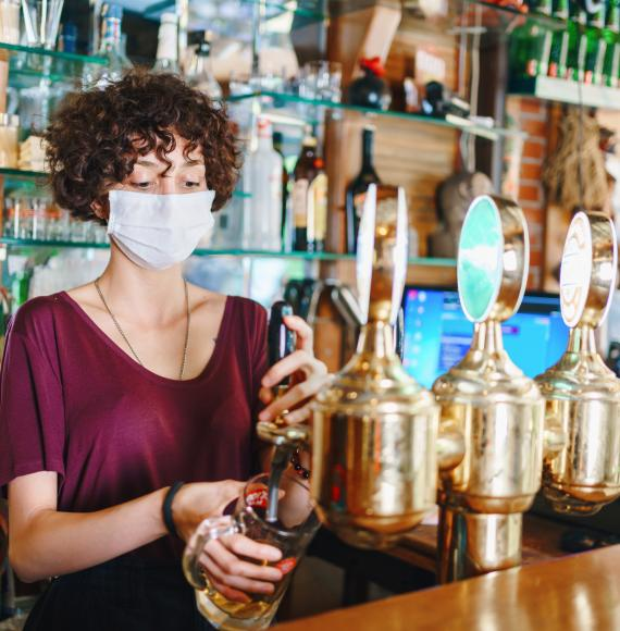 Woman with face mask pulls a pint