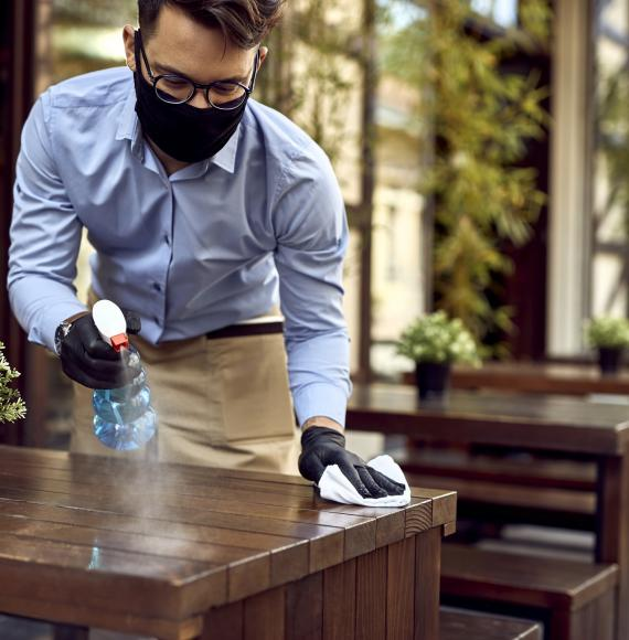 Waiter cleans table with antibacterial spray and wipe.
