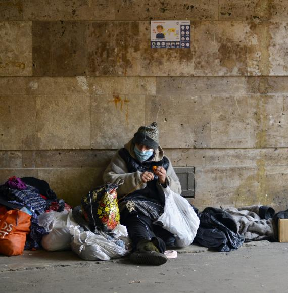 Homeless person sits against the wall in winter.
