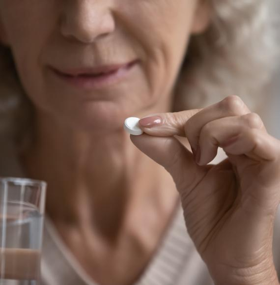 Elderly woman holds pill in her hand ready to be taken.