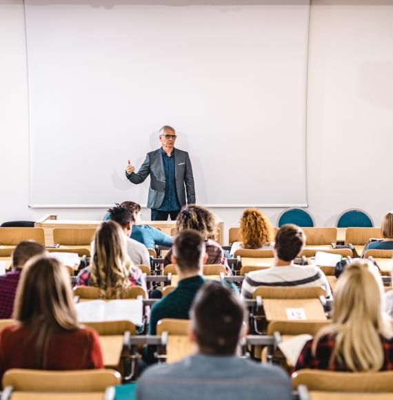 Lecturer stands teaching students in a lecture hall.