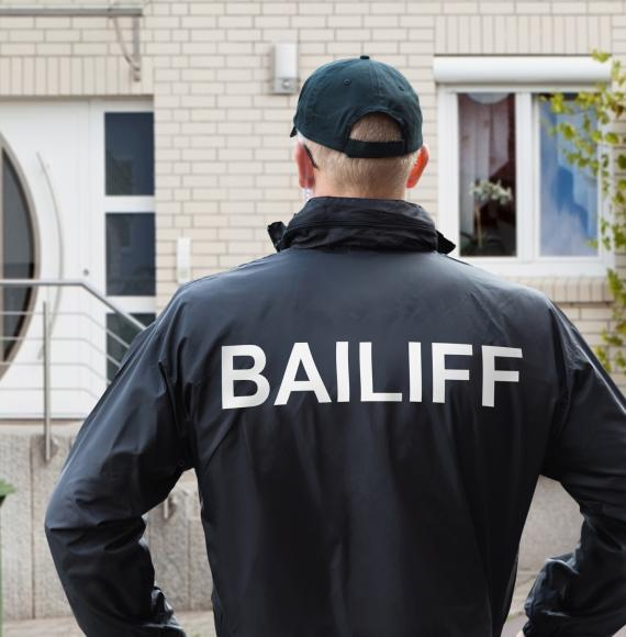 Bailiff stands in front of house ready to knock.
