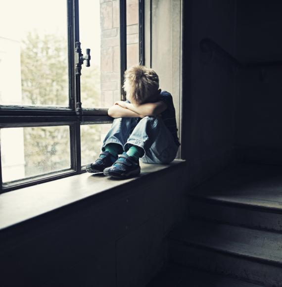 Lonely child sits in window.