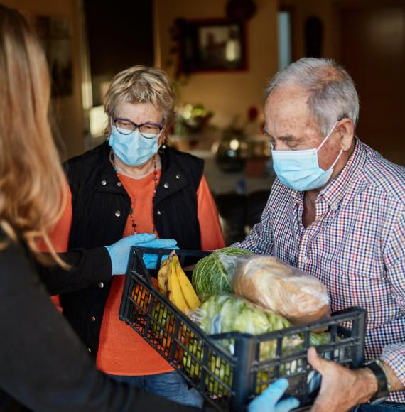 Elderly couple receive food parcel during pandemic.
