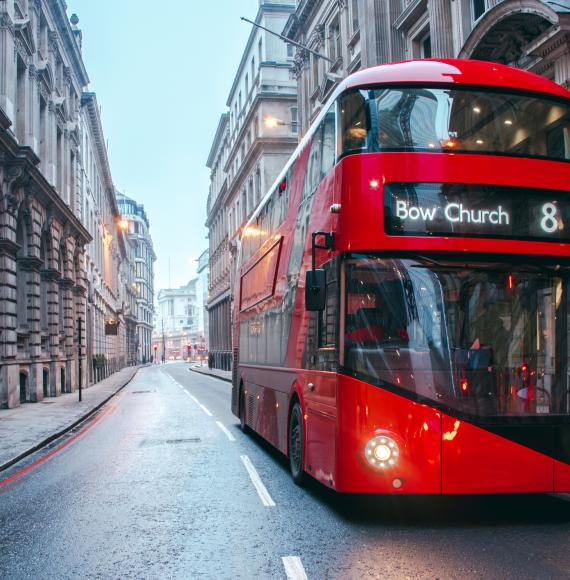Bus drives down empty London street.