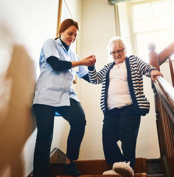 Social care worker helping woman walk down stairs